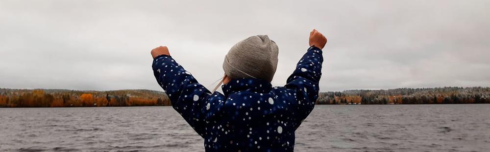 Ympäristökasvatuksen uutiskirjeen kuvituskuvana on iloinen lapsi järven äärellä.